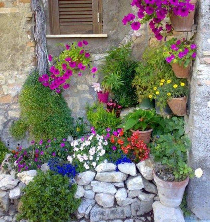 pétunias suspendues et des fleurs dans des pots à fleurs en terre, rocaille fleurie dans un coin exterieur maison, amenagement jardin miniature style méditerranéen