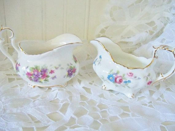 A lovely pair of English bone china cream jugs. One is Royal Albert Violetta and the second is by Hammersley, both made in England.  Sizes