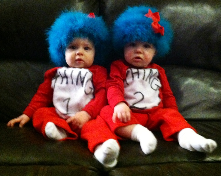 Thing 1 and Thing 2 -Dr Seuss. Twin Halloween costumes. I cut a felt circle, wrote with fabric marker, then sewed to the red long sleeve tee (purchased tee and matching pants from Old Navy for $14/set). Bought a $4 crocheted blue hat and $4 aqua feather boa from Hobby Lobby. Hand sewed boa to hat loosely. Used red bows for my girls. Twin girls halloween costume.