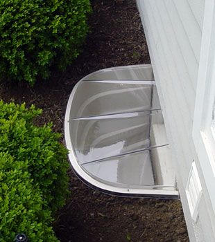The Sunhouse basement window well system. Helps protect your basement windows, and also brightens up your basement living space! I love this idea.