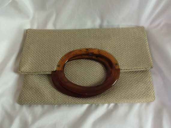 Vintage foldover woven purse with dark brown plastic handles.