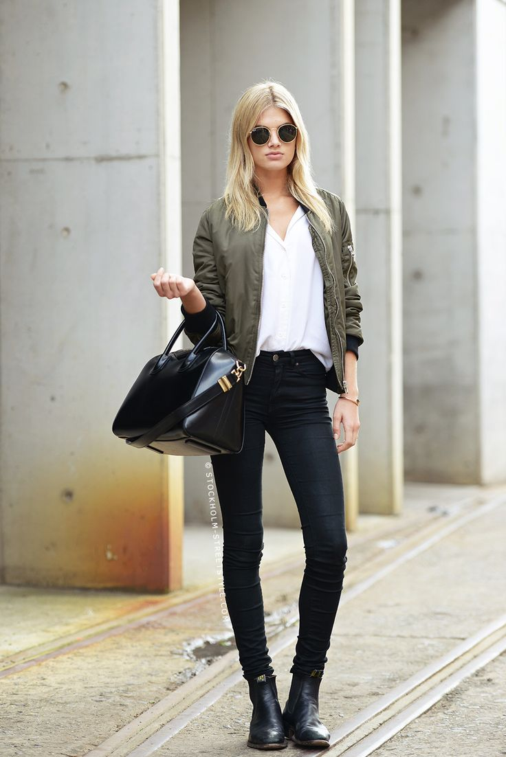 olive green bomber jacket, white top, black high waisted skinnies and black boots.