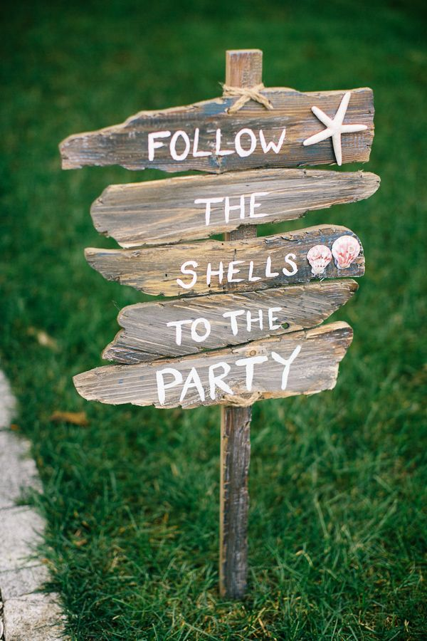 """Follow the shells to the party!"" beach wedding sign."