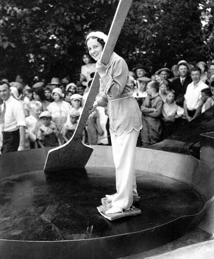 Woman in a giant frying pan with bacon tied to her feet before 7200 eggs are added to a record breaking omelette, Sweden, Nov 1931.