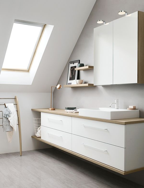 Utilise the asymmetrical to your advantage. Choose a counter top and combine with floating shelves under the sloping wall.