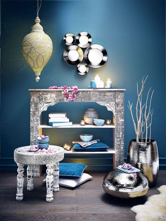 So kann der orientalische Stil auch umgesetzt werden. Die orientalischen Accessoires in silber vor einer blauen Wand.