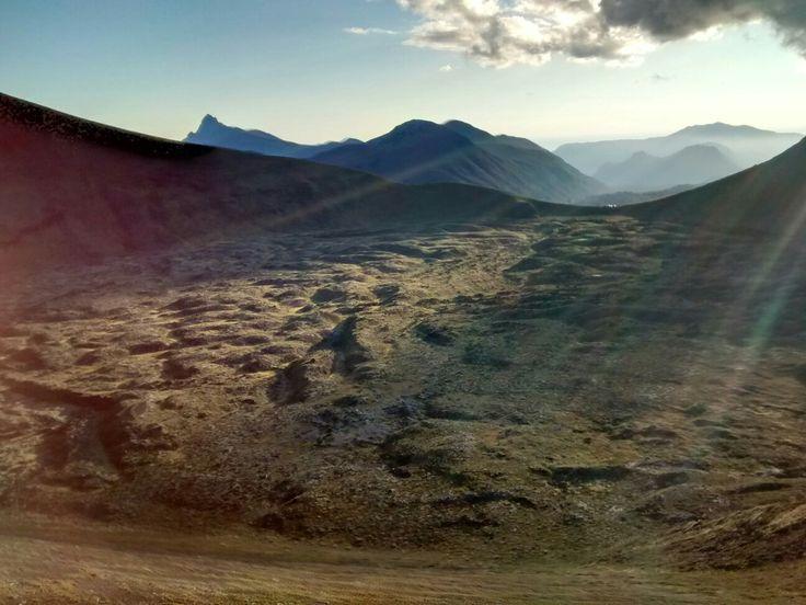 Suaves rayos de sol caen sobre la superficie del Cráter Raiwen, Osorno, Región de Los Lagos, Chile. Al fondo y a media izquierda,  se eleva el Cerro Sarnoso.