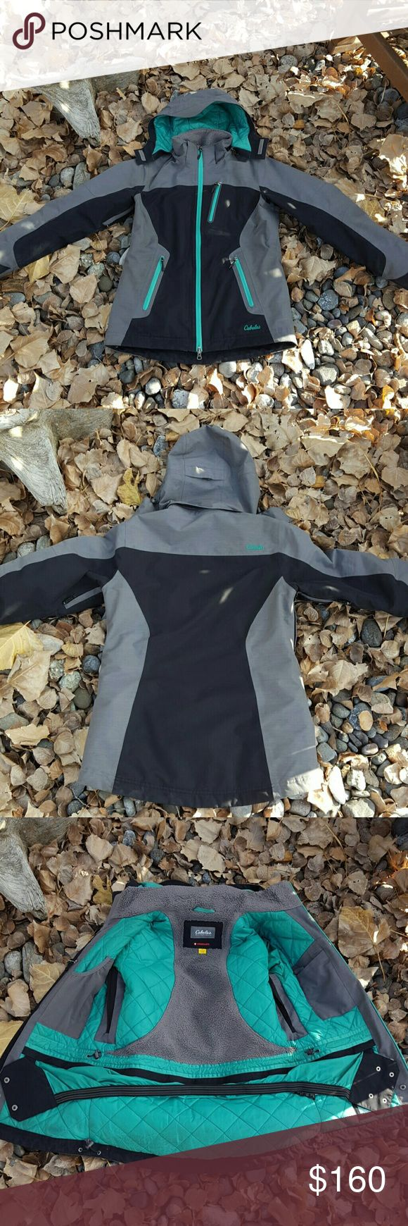 Cabelas Women's Winter Jacket w/ Goretex Cabelas  Women's Winter Jacket  Goretex  Primaloft  Size S/P Black, Gray, & Turquoise Color Detachable Hood, Hood also has adjustable cincher and velcro front to block wind if needed 2 Front Bottom Pockets, 1 Upper Chest Pocket, 1 Pocket on Arm for ski pass or ID  Zipper Arm Vents 3 inside Pockets  (1 mesh pocket, 1 ipod/cell phone pocket, 1 zipper pocket) Soft Inside Lining Powder Skirt Cinchable Waist and Bottom to keep snow & cold out Worn spots…