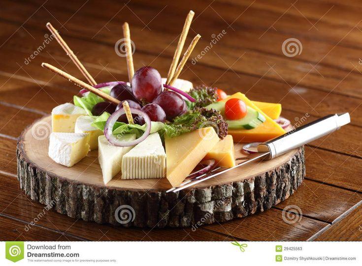 Plato de madera con queso y frutas