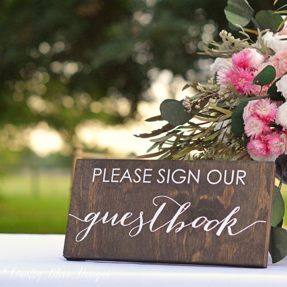 This wooden Please Sign Our Guestbook sign measures approximately 11 x 5.25. The lettering is painted in white on dark walnut wood.