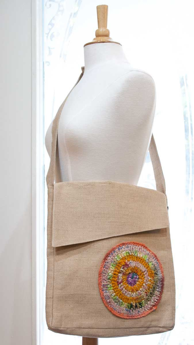 This jute messenger bag is lined with cotton and is embellished with a hand crocheted patch made from recycled sari silk. Purchases of these bags help young women in India who have been given vocation