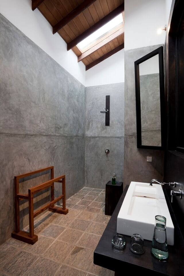 Ein robuste und rustikale Badezimmer überschwemmt mit grau gewaschene Wände zwischen strukturierten Fliesen-Böden und eine schräge Holzdecke. Natürlich, sticht der dunkle Eitelkeit Zähler aus dieser robusten Look.