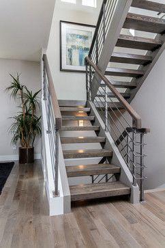 Grey hardwood floors with open staircase & steel railings
