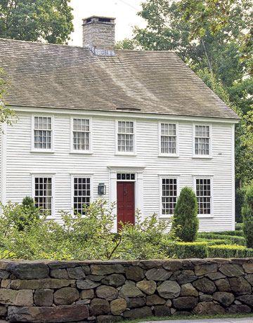 Classic white Colonial, red door, small pane windows, center chimney, granite stone wall.