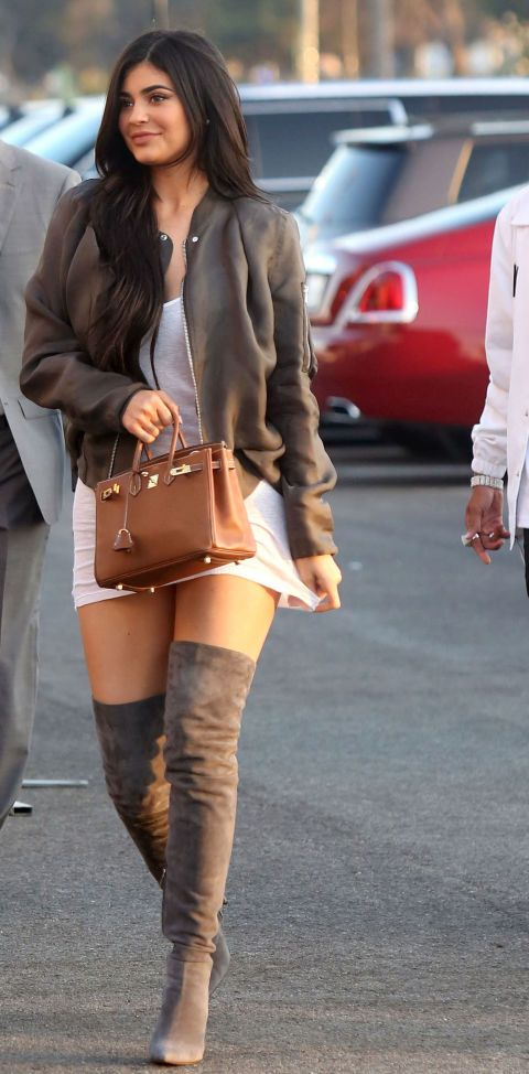 Kylie Jenner at Kanye's 'Famous' music video screening in a white IRO slip dress, a light brown bomber jacket, light brown over-the-knee Gianvito Rossi boots and an Hermes bag.