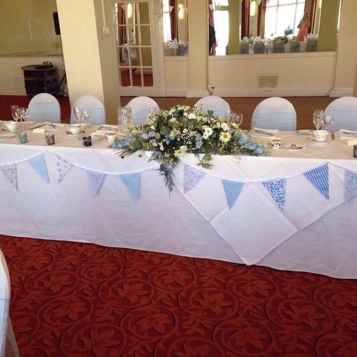 Top table. Pastel blue bunting and floral arrangement by Minnie Bees.