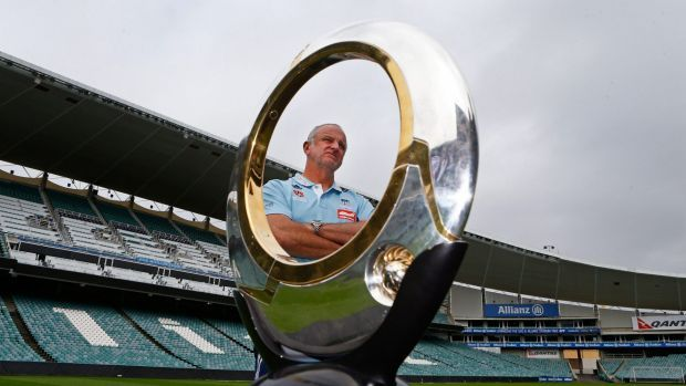 Graham Arnold is seen behind the A-League trophy at Allianz Stadium.