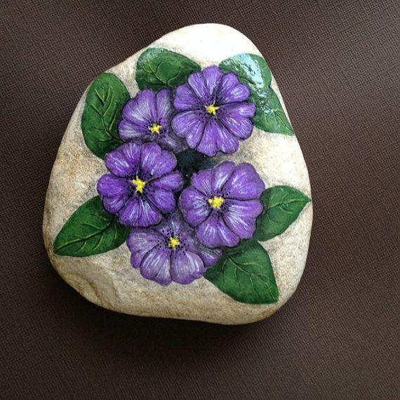 Roca pintada de flores de violeta, violeta de la primavera de la mano