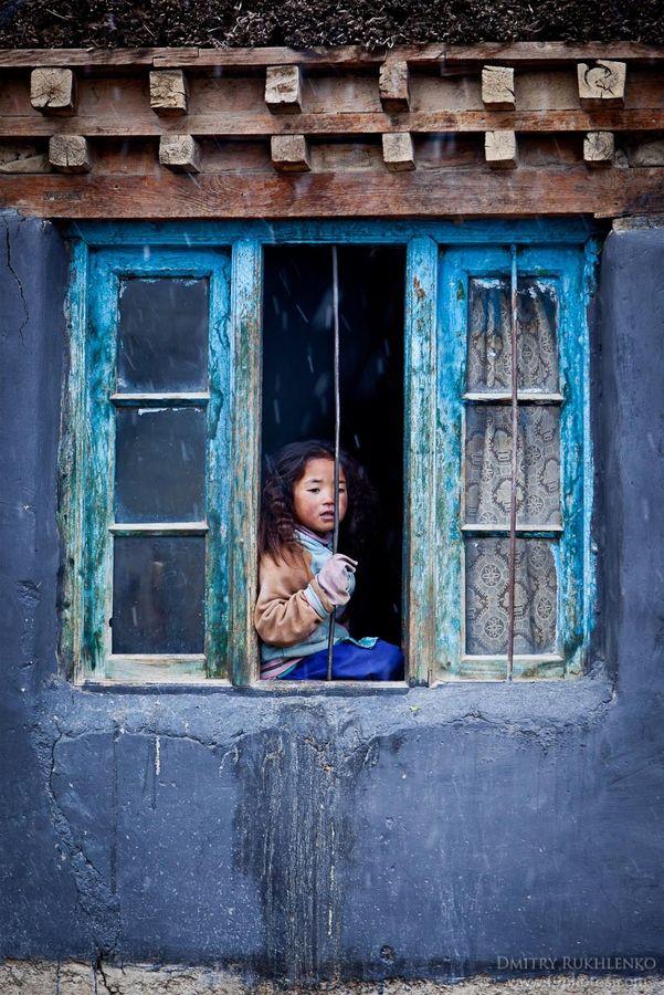 Chica por la ventana en el pueblo de Kibber, Valle de Spiti, Himachal Pradesh, India