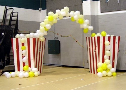 Yellow/white balloon arch + red and white striped pillars  =  giant popcorn buckets!!!