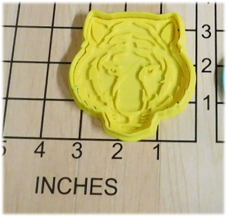 Tiger Shape Fondant Cookie Cutter and Stamp #1026. Tiger Fondant Cookie Cutter and Stamp. This 3d printed plastic cutter makes the shape of a tiger's face. Some uses for this cutter are cookie dough, play doh, or fondant.The Stamp is made separately to accommodate any thickness of dough. Actual measurements can be seen in photo. Color of plastic will vary according to availability and may be different than shown. Please Note: Play Dough Sample Cookie is NOT INCLUDED.