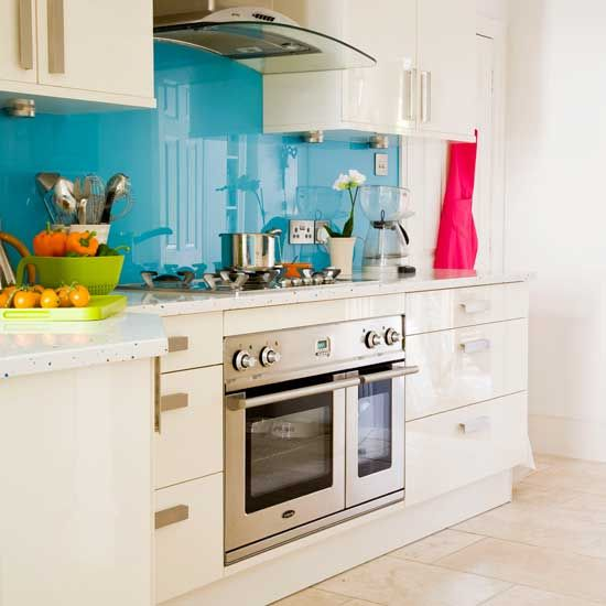 Blue splashback kitchen Add a shot of vibrant colour in a white kitchen with a glass splashback. This indigo shade gives the light and airy space, along with the hi-gloss material, a contemporary feel. Team with sleek appliances and modern kitchenware in zesty shades for a super-modern look.