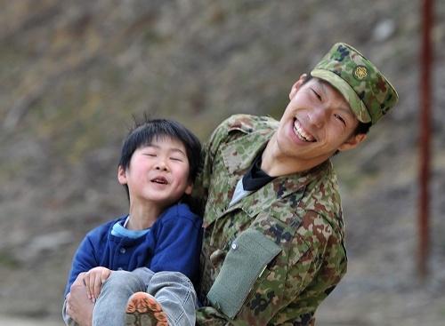 避難所の子どもの遊び相手になって笑顔を見せる自衛隊員=宮城県南三陸町で2011年4月3日午後4時11分、三浦博之撮影