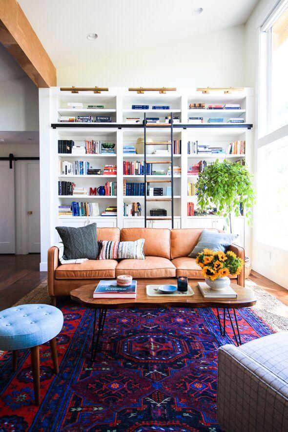 Beautiful bookcase. West elm sofa. Sunflowers. Pop of color.