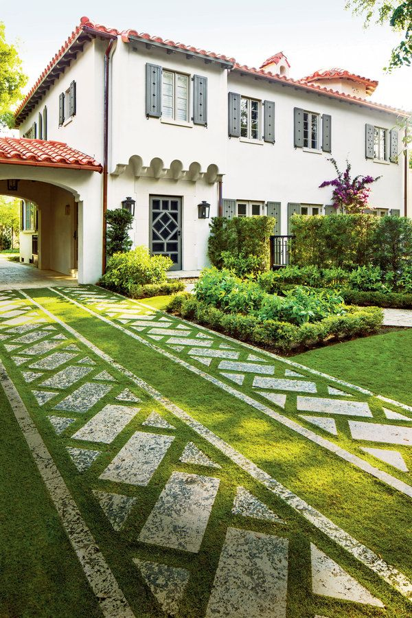 Driveways nearly always consist of utilitarian carpets of blinding-white concrete, but doing that would have been a crime in this yard. Instead, two tracks of cut stone were placed on the diagonal between straight courses of stone that were run from the street to the porte cochere and the parking area in back. Soft, green grass grows between the stones, reducing heat and glare. Fully functional and also beautiful, it creates a grand approach.     See more of this Coral Gables Garden