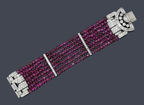 RUBY AND DIAMOND BRACELET, VAN CLEEF & ARPELS, ca. 1934. Platinum. Very fancy bracelet of numerous, seven-row fine ruby spheres of ca. 3 - 4 mm Ø. The asymmetrical clasp designed as a stylized buckle set throughout with 3 crescent-shaped diamonds weighing ca. 2.00 ct, 37 baguette-cut diamonds weighing ca. 4.00 ct, 5 brilliant-cut diamonds weighing ca. 0.80 ct, 16 carré-cut diamonds weighing ca. 0.80 ct and 96 pavé-set brilliant-cut diamonds weighing ca. 2.50 ct. Two additi...