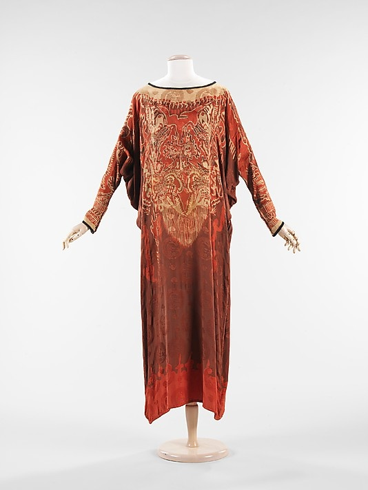 """Evening Dress: ca. 1920, American or European, silk. """"This evening dress is an example of the ongoing fascination with Eastern and Middle Eastern cultures that prevailed in the early 20th century. The garment itself reflects a mix of influences with its caftan shape, batik-style print, and use of Chinese motifs. The finishing details reflect a high level of quality and the use of batwing sleeves are an intriguing feature."""""""