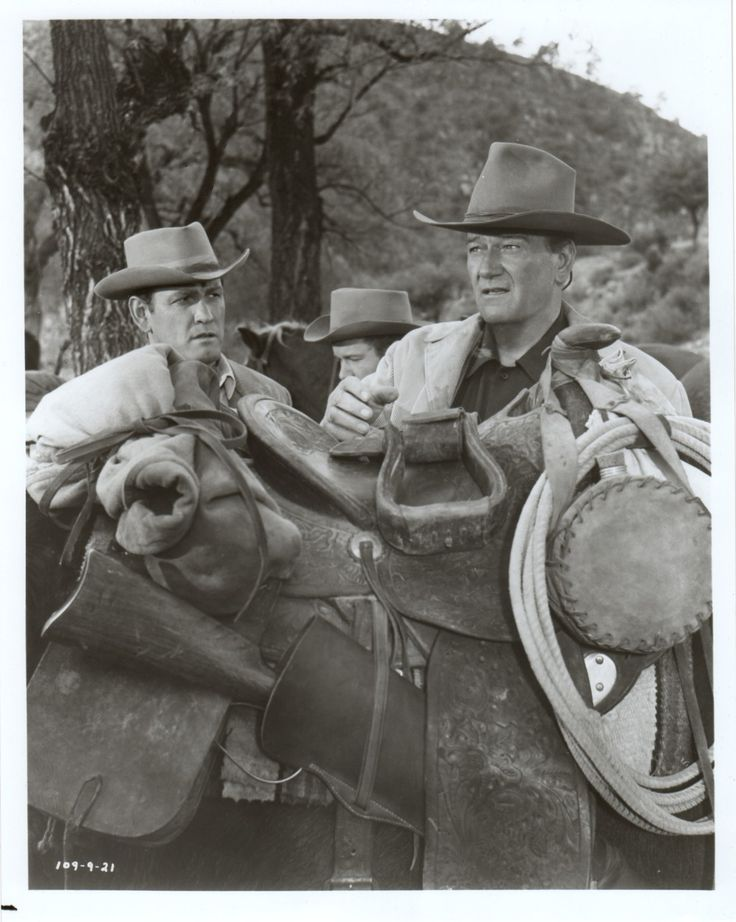 THE SONS OF KATIE ELDER (1965) - Earl Holliman talks with John Wayne as he adjusts his saddle - Directed by Henry Hathaway - Paramount Pictures - Movie Still.