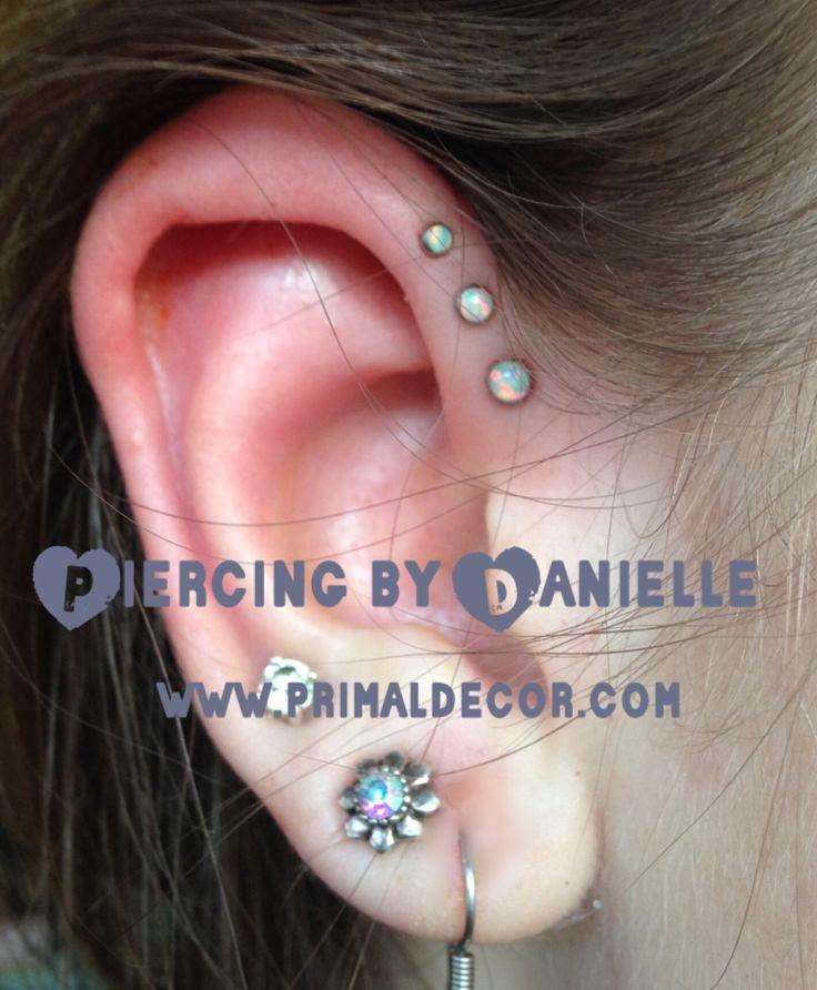 Triple forward helix piercing with white opals in graduated sizes. Jewelry by Neometal.  www.primaldecor.com