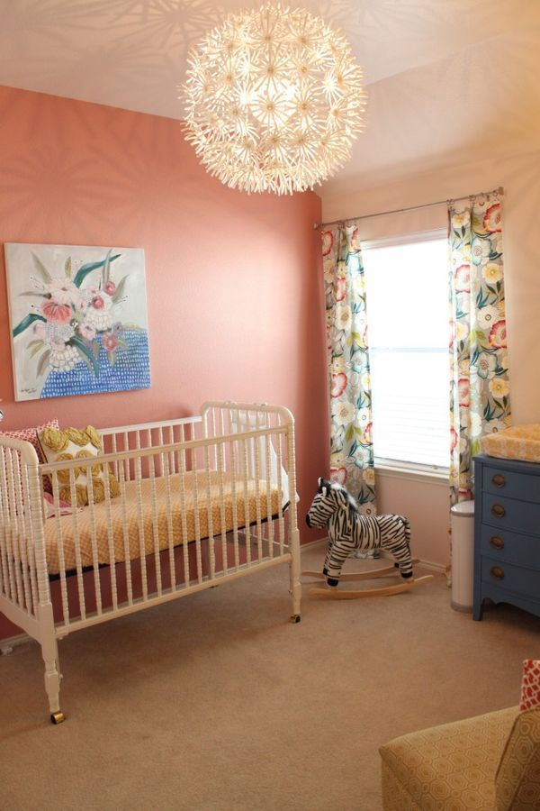 Beautiful Coral Accent Wall Paired with Floral Decor in this Baby Girl Nursery