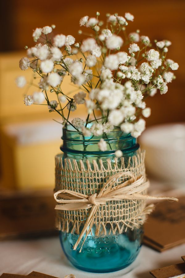 blue mason jars filled with baby's breath and wrapped with burlap add a rustic touch to weddings and receptions - thereddirtbride.com - see more of this wedding here