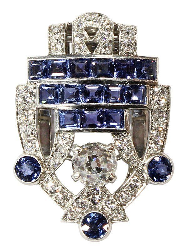An Art Deco sapphire & diamond clip brooch, Cartier, ca 1930; the openwork shield highlighting an Old Mine cut diamond, weighing approx 1.15 cts; embellished with Old European cut diamonds, round mixed & square step cut blue sapphires;