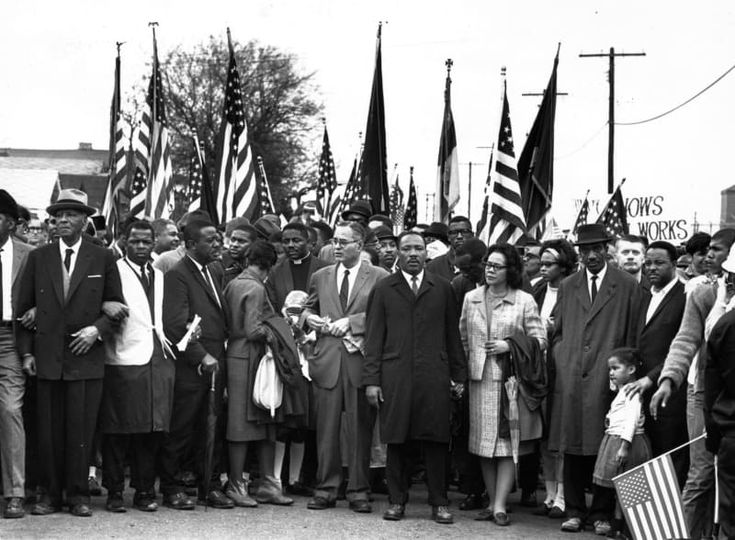 Dr. Martin Luther King marches with his wife, Coretta Scott King, and a crowd of supporters from Selma, Alabama, to the state capital in Montgomery, to call national attention towards black voting rights in March, 1965.