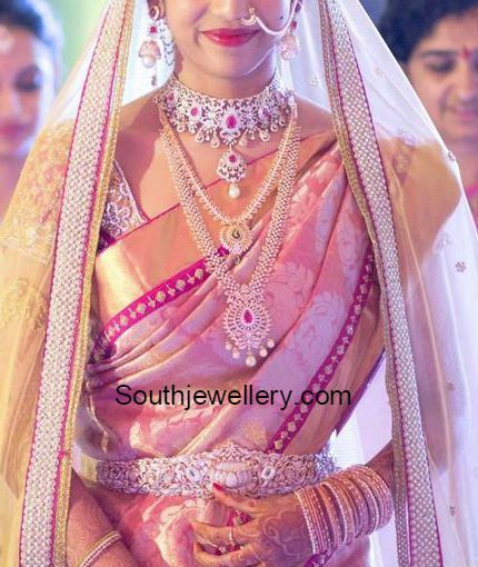 South Indian bride in diamond jewellery. She adorned a ruby diamond choker and jhumkas set, diamond long chains and diamond vaddanam.