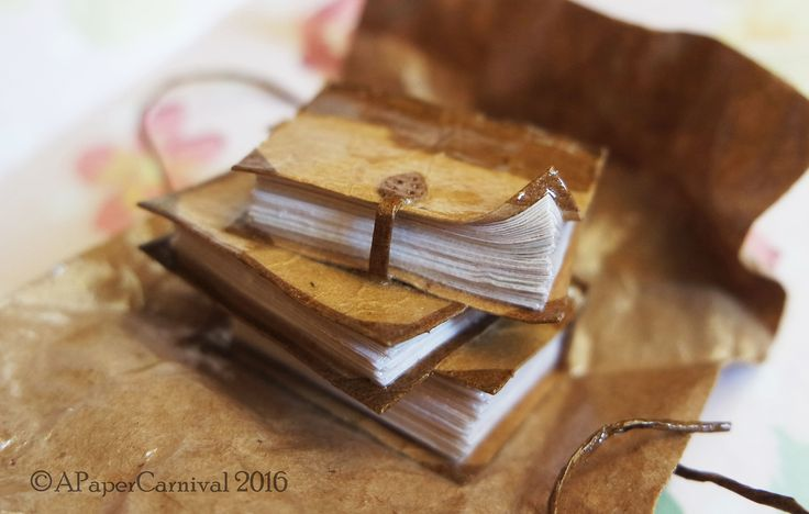 Handmade by Rachel Prout. A miniature stack of old novels in brown paper and twine.
