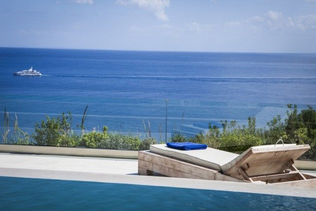 The large, inviting, infinity-edged swimming pool is surrounded by a wide paved terrace which is both secluded and open to amazing views