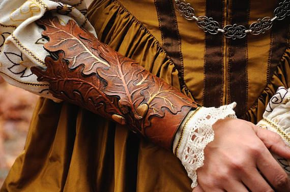 A pair of decorative bracers inspired by the oak tree motif  Its one of ours best designs. Very beautiful and laborous leatherworked. Thick leather carved and deeply punched (and painted). You can hang your pitbull with his teeth on this piece of art! :)  It can be in brown, green, or metallic version - you choose.  Designer: Magdalena #leather #leaf #leatherleaf #leatherbracer #bracer #silverclock