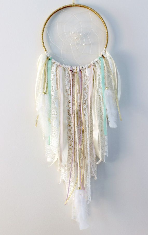 Pastel and Gold Unicorn Dream Catcher  So soft and pretty! This dream catcher would make the perfect tribal party decor for a birthday or baby shower. Would look stunning in a gold and pastel nursery as well. Hoop is wrapped in gold ribbon and the web is handwoven in cream cotton. Your dreamcatcher will have 3-9 pearls in the web depending on the size you choose. The bottom is packed with cream lace with pastel accents of pink, gold, lavender, and mint. The soft white feathers are attached…
