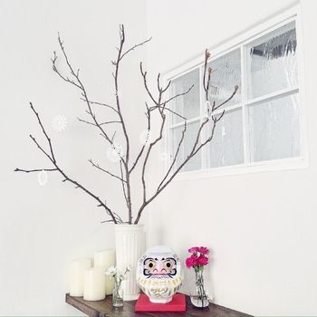 新しい年の願い事や目標のこめてお正月に買う、だるま。飾るだけで、お正月の雰囲気が出ます。こちらは、手作りのペーパークラフトだるま。フラワーベースやキャンドル、オーナメントなど白で揃え、ピンクのお花と土台を挿し色にして、ハイセンスなお正月飾りに仕上がっています。