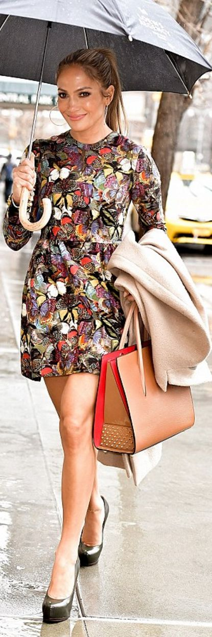 Who made Jennifer Lopez's tan tote handbag, purple butterfly print dress, and black platform pumps?