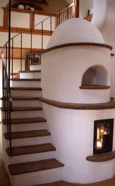 Stairs wrap around a masonry heater.