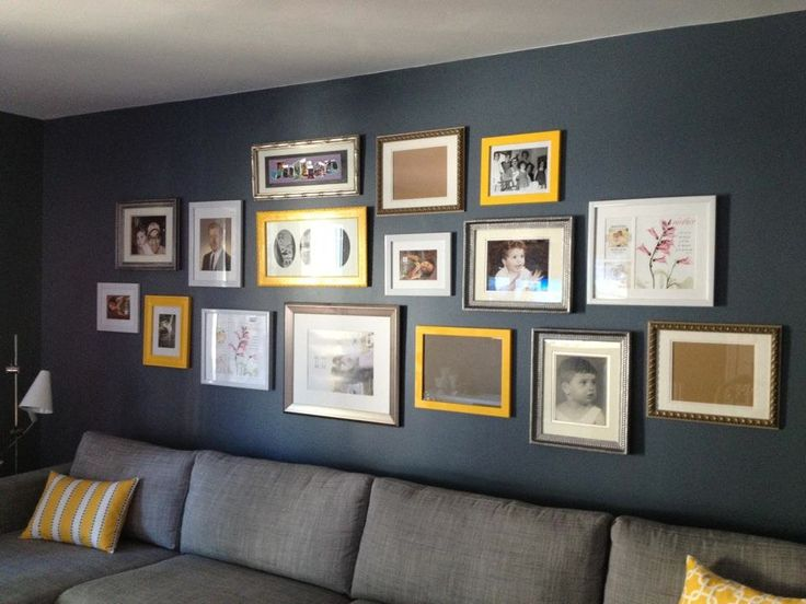 Frames + photos + wall of photo frames + wall of frames + yellow + grey + grey couch + yellow pillows - wall of photo frames with yellow/grey theme - our family room