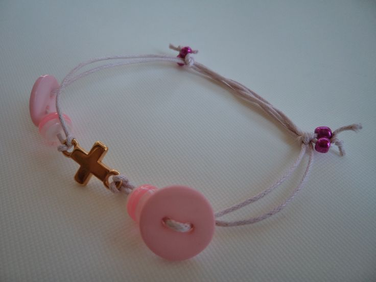 Pink wax cord bracelet with a gold metallic cross, two pink buttons and pink beads.