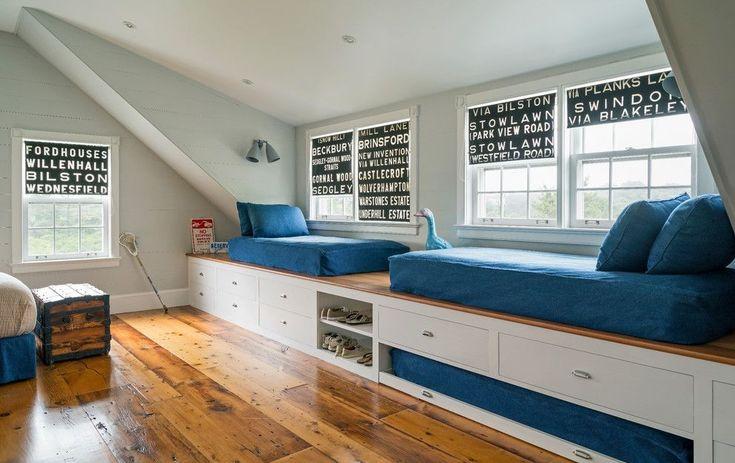 Cette chambre d'enfant sous comble est pourvue de plusieurs lits. En prime, un matelas est caché sous l'estrade sur un grand tiroir : il est ainsi facile d'accueillir des amis supplémentaires !
