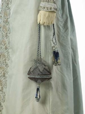 (Matching reticule detail) A pelisse or pelisse-coat, a kind of women's outer garment which could be made in everything from the lightest silk to heavy fur. It was worn over a gown but could look like a gown itself, especially when floor length like this garment. The pelisse was made for a trousseau in 1823 for the wedding of the grandmother of the donor.: