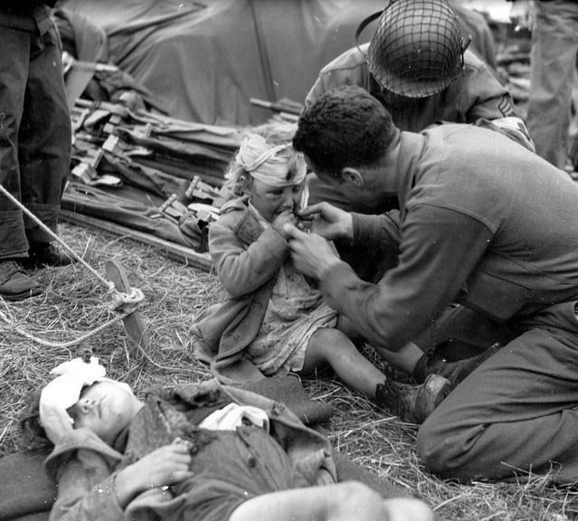 army medics | US Army medic gives candy to an injured child. France, July 1944.  Photo: Conseil Régional de Basse-Normandie / National Archives USA